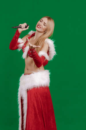 Young girl Santa Claus with long hair singing in a microphone and posing on a green background