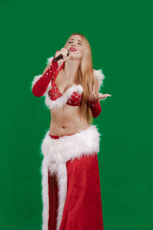 Young girl Santa Claus with long hair singing in a microphone and posing on a green background Stock Photo
