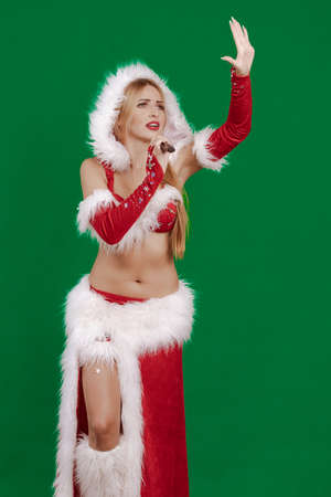 Beautiful emotional young girl with long hair in a costume of Santa Claus with a microphone in hand sings on a green background