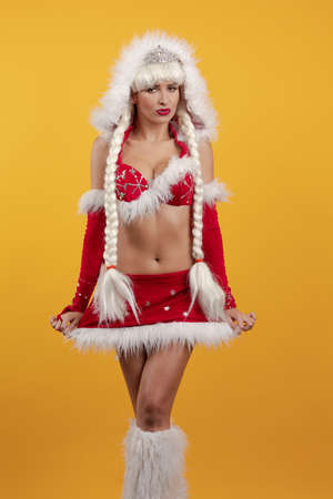 Beautiful emotional young girl dressed as Santa Claus and with long braids hairstyle posing on a yellow background 免版税图像