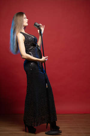 Young woman with long hair in a black dress on a red background. The singer in a glamorous manner sings into the microphone and performs on stage.