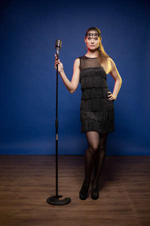 Young woman with long hair in a black dress in a retro style on a blue background. The singer sings into the microphone and performs on stage.