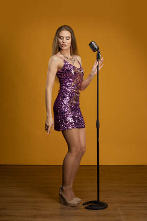 Young woman with long hair in a short purple dress on a yellow background. The singer sings into the microphone and performs on stage.