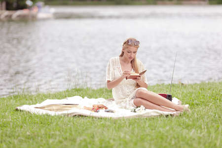 A young girl in a white dress reads a book and has a picnic. On the green grass by the lake on a sunny summer day.