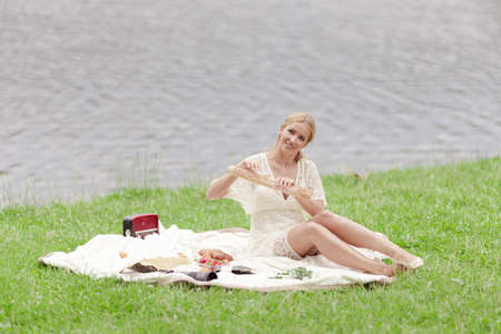 A young woman in a white dress eats strawberry fruits and drinks champagne and rests on a picnic. On the green grass by the lake on a sunny summer day. Stockfoto
