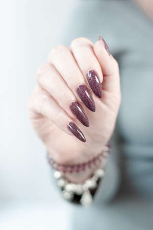 Woman hand with long nails and a bottle of dark brown red nail polish