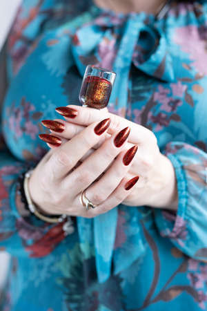 Female hand with long nails and golden brown maroon, manicure holds a bottle of nail polish
