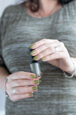 Woman's hand with long nails and light and dark green manicure with bottles of nail polish