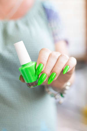 Female hand with long nails and neon green manicure with bottles of nail polish