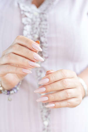 Woman hand with long nails manicure and light pink bottle with nail polish