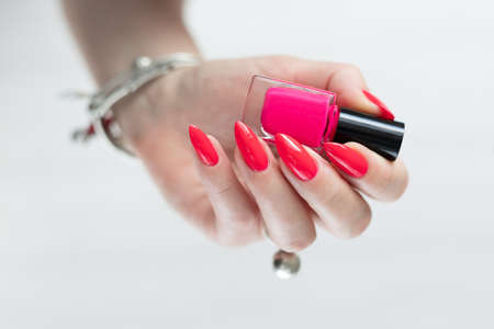 Female hand with long nails and a bottle bright neon pink red color nail polish