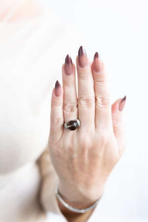 Female hands with long nails with light pink and burgundy nail polish