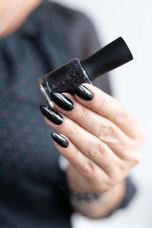 Female hand with long nails and black manicure holds a bottle of nail polish