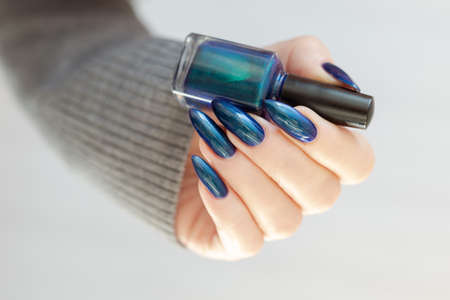 Female hand with long nails and bright blue manicure with bottles of nail polish