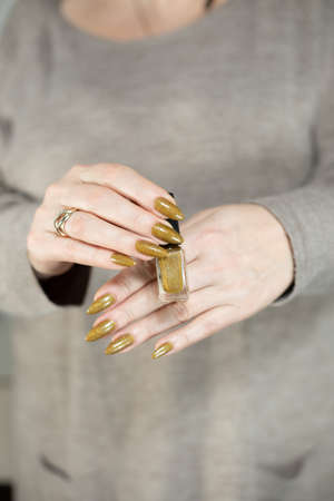 Female hand with long nails and a bottle of bright yellow green nail polish