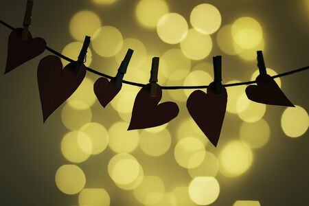 Cardboard hearts hung with small tweezers and rear bokeh