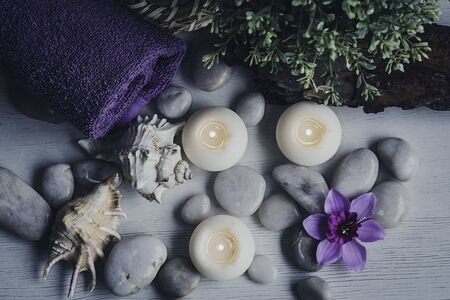 Conch shells, stones and candles with rolled towel as in a spa session