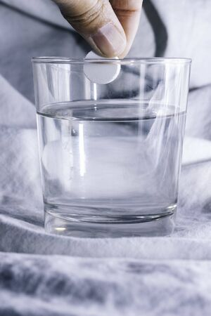 Hand about to throw an effervescent tablet into the water Glass of water with medication. Disease concept