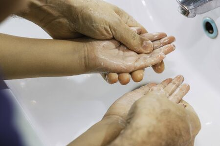 Dad washing his little son's hands with soap and water