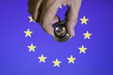 Hand with stethoscope auscultating European Community flag Conceptual Covid-19 crisis, reconstruction europe Banco de Imagens