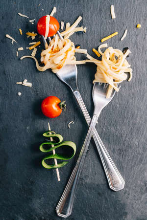 Pair of forks with rolled spaghetti, cherry tomatoes and zucchini Conceptual of healthy food, new trend veganism 스톡 콘텐츠