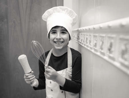 Smiling boy poses in the kitchen of his house with chef uniform
