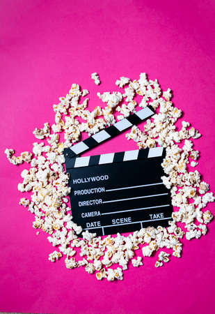 Movie clapperboard and popcorn on fuchsia pink background