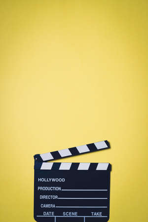 Movie clapperboard on yellow background