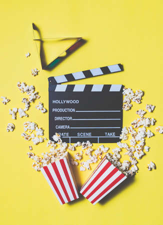 Movie clapperboard and popcorn on yellow background 写真素材