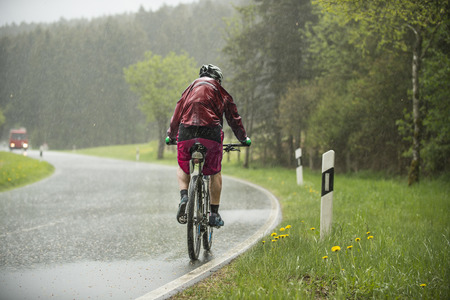 Man drives up on the bicycle in the flowing out rain an increase