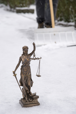 When do you have to clear the snow? - Justitia statue in the foreground, in the background a man is clearing snow off the sidewalk Stock Photo
