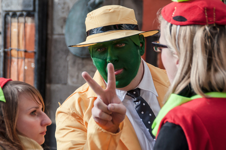 Cologne, Germany - March 14th 2014: A man wears the costume from the movie The Mask, a yellow suit with a yellow hat and green face