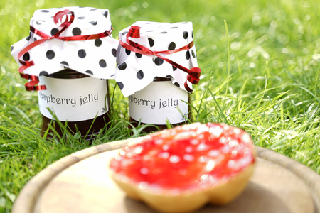 2 glasses with homemade raspberry jelly stand on sunny green meadow. The labels show the text: Raspberry Jelly. They are decorated with dotted paper hoods. In the foreground is a wooden plate. On it i