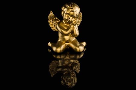 Golden angel in front of black background