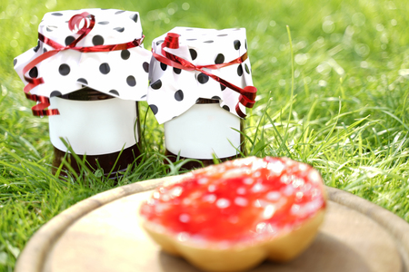 2 glasses with homemade red jelly stand on sunny green meadow. They are decorated with dotted paper hoods. The labels offer Copy Space. In the foreground is a wooden plate. On it is a roll. It is cove 写真素材