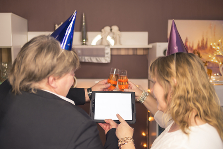 Couple watching during New Years Eve party at a Tablet PC