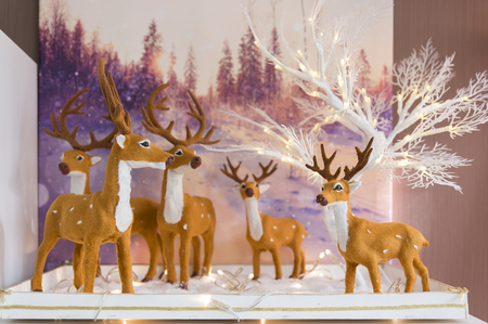 Brilon, Germany - November 17th 2017: Winter decoration for at home - winter forest and deers lights up with Christmas tree Publikacyjne