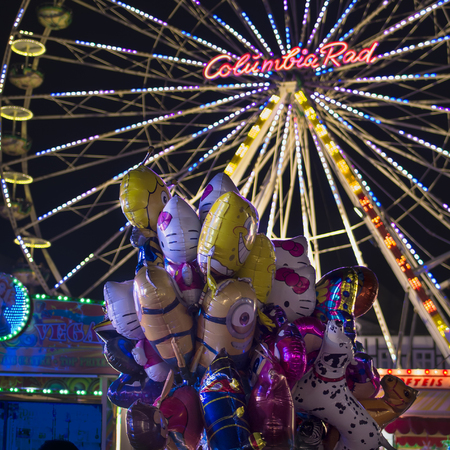 Brilon, Germany - September 22nd 2017: Michaeliskirmes (Michaelis funfair) in the evening - the ferris wheel glowes and there are foliage balloons of comic heroes