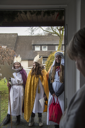 Brilon, Germany – January 6th 2018: Three holy kings -  three girls stand at the doorstep as the Three Wise Man and collect donations