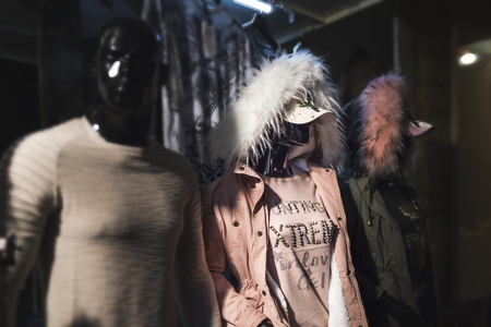 Stylish clothes on mannequins in the dark