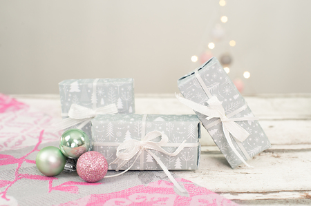 Small gifts wrapped in gray white paper stand in Christmas atmosphere. Pastel colored tablecloth and small christmas balls on white wooden background. Copy Space