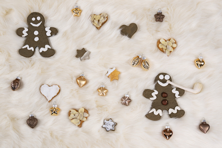 Gingerbread men and shortbread cookies in form of stars and hearts lying together with golden Christmas baubles on a white lambskin. Photographed from above.