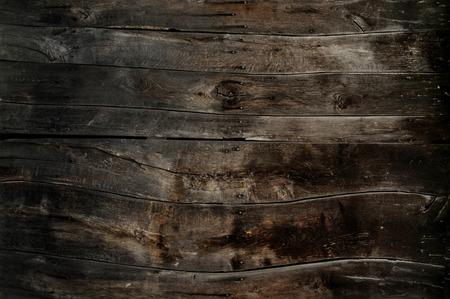 Several wooden beams are next to each other and fill the picture. They have a nice dark color, are very old and weathered.