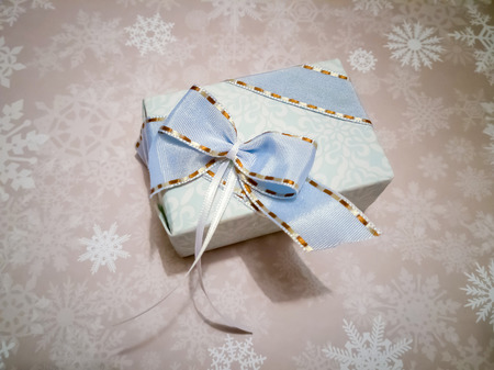 Noble Christmas present is wrapped in pastel colored paper. The present has a loop. It probably has high quality content.