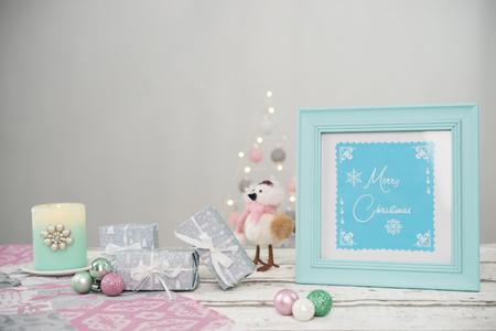 Christmas decoration elements stand on a wooden background. A little funny bird and a sign with the text: Merry Christmas are unusual.