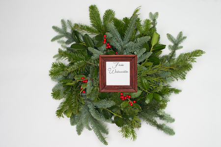 A circle of branches of different fir varieties. Green and blue firs. A brown frame shows the german text: merry christmas.