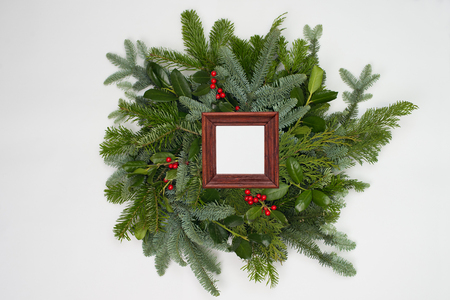 A circle of branches of different fir varieties. Green and blue firs. A brown frame give copy space for own design.