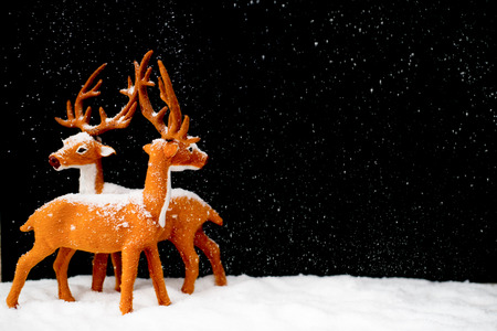 2 Figures that look like deers are standing in the snow. Its snowing. Black background.