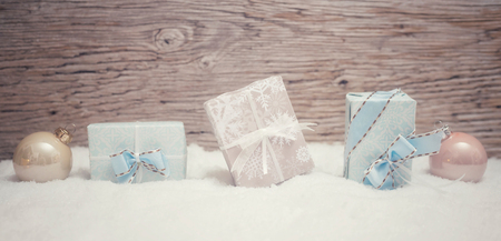 3 small Christmas presents stand in pastel colored fine wrapping paper in the snow. Wooden background