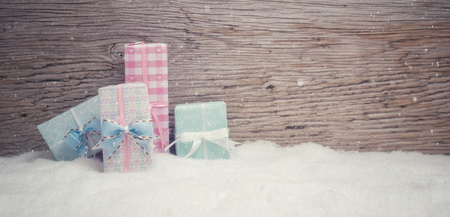 4 small Christmas presents stand in pastel colored fine wrapping paper in the snow. Wooden background with snowfall